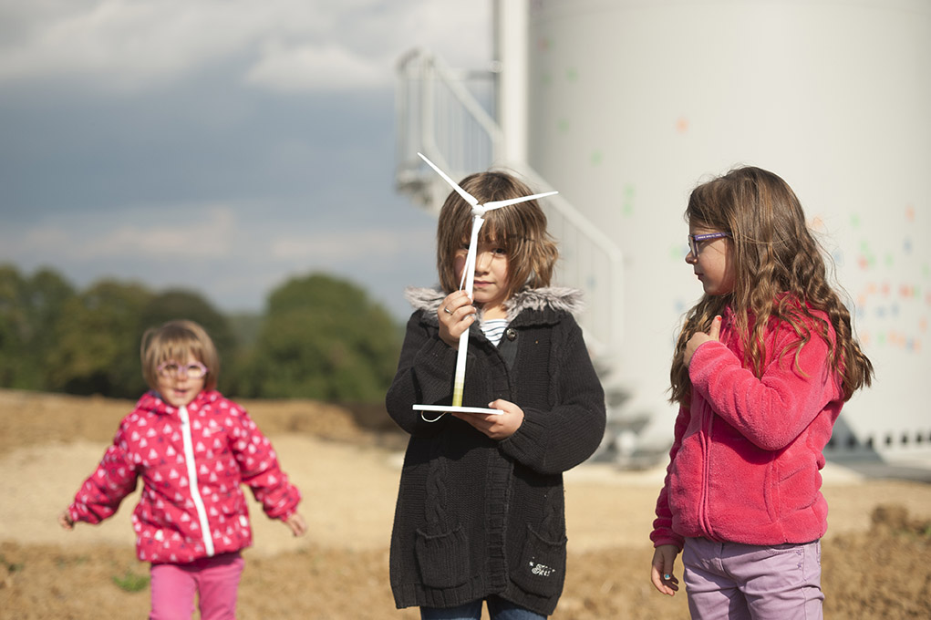 trois enfants portant une maquette d'éolienne avec éoliennes en fond